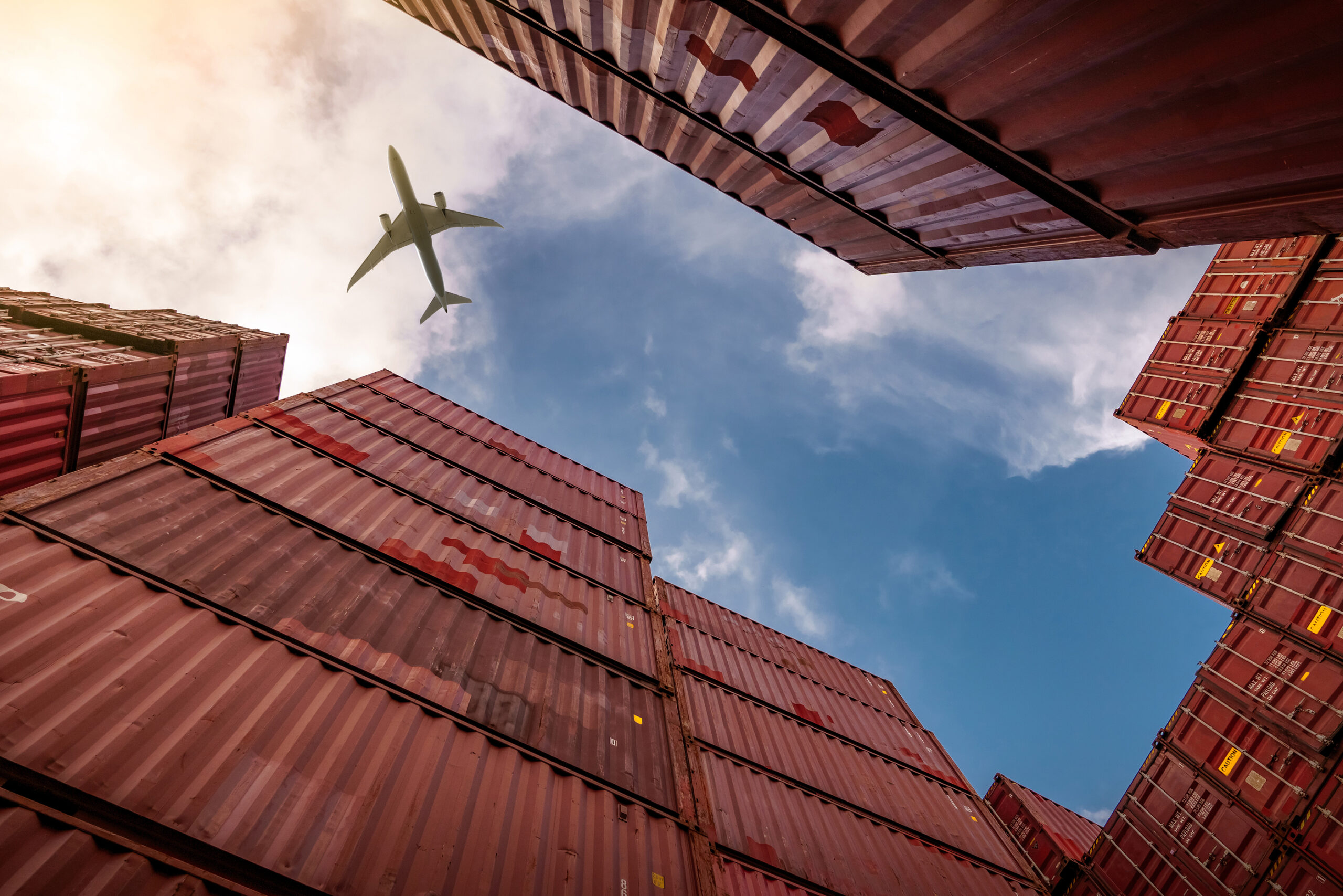 Airplane flying image n the sky above storage containers