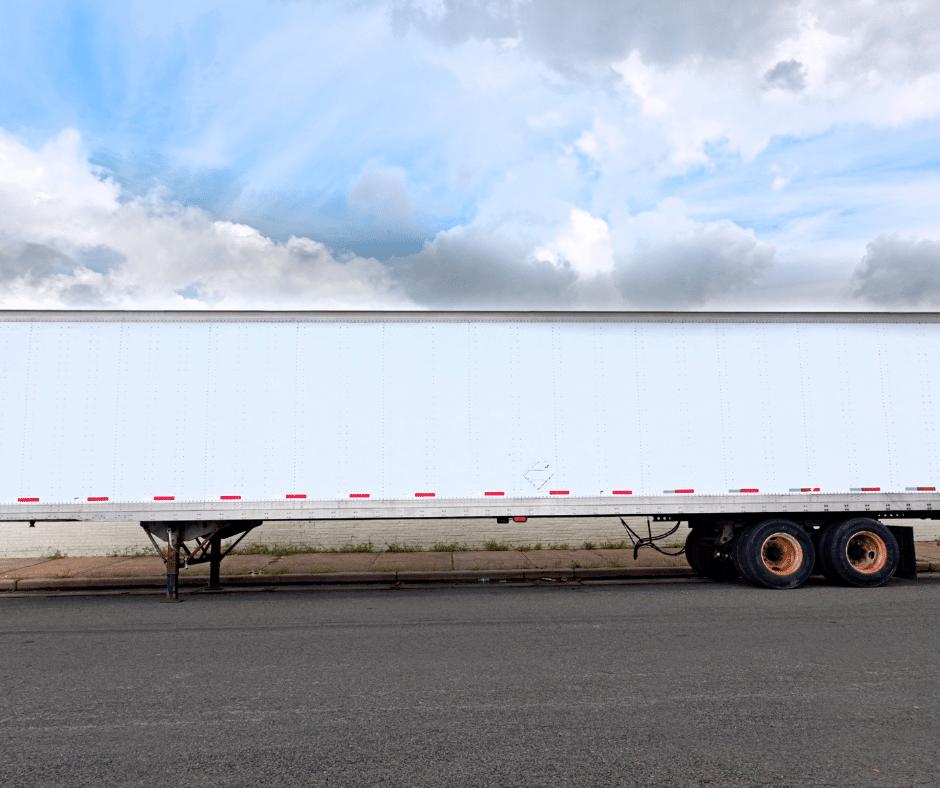 A white storage trailer against a cloudy blue sky.