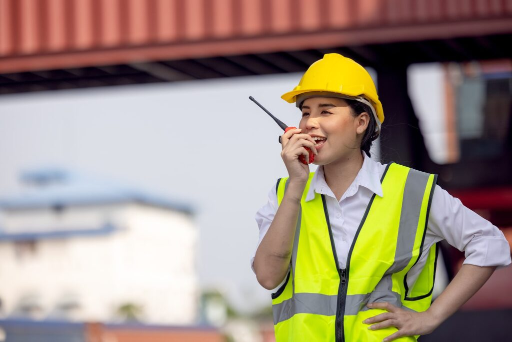 A woman at a warehouse site with storage containers in the background.