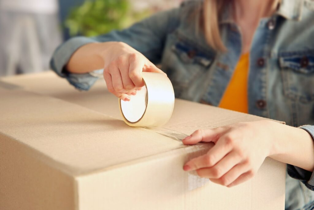 A person sealing a cardboard box with packing tape.